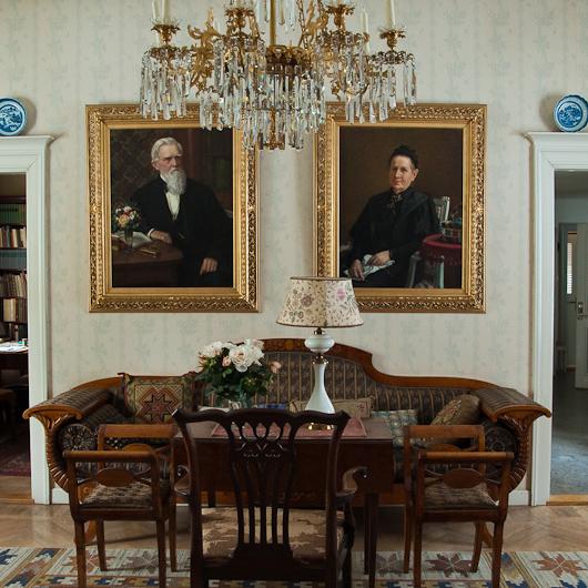 bild från ett av husets rum där vi ser en soffa, bord och två stora tavlor på väggen