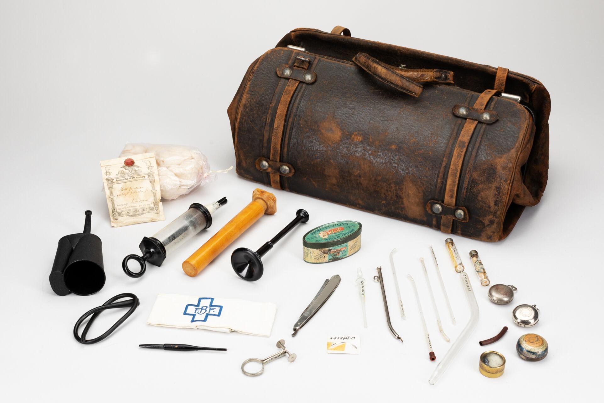En gammal skinnväska. I förgrunden en mängd verktyg avsedda för barnmorskor. Spruta, armbindel, fetvadd, pipett