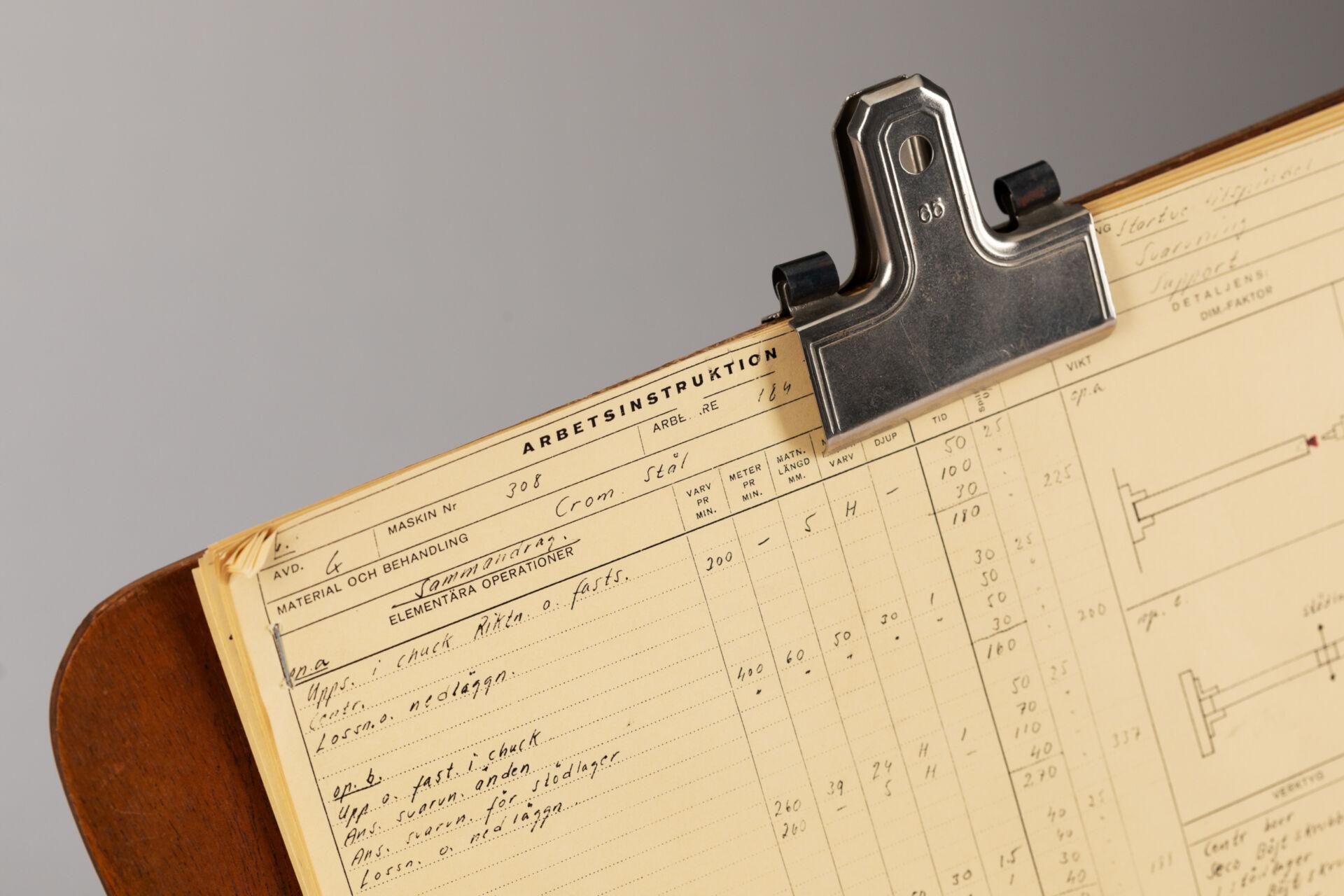 Tidsstudiebräda på metallarm. Inklusive tidsstudieblanketter fastsatta med pappersklämma. För tidsstudier vid varven.