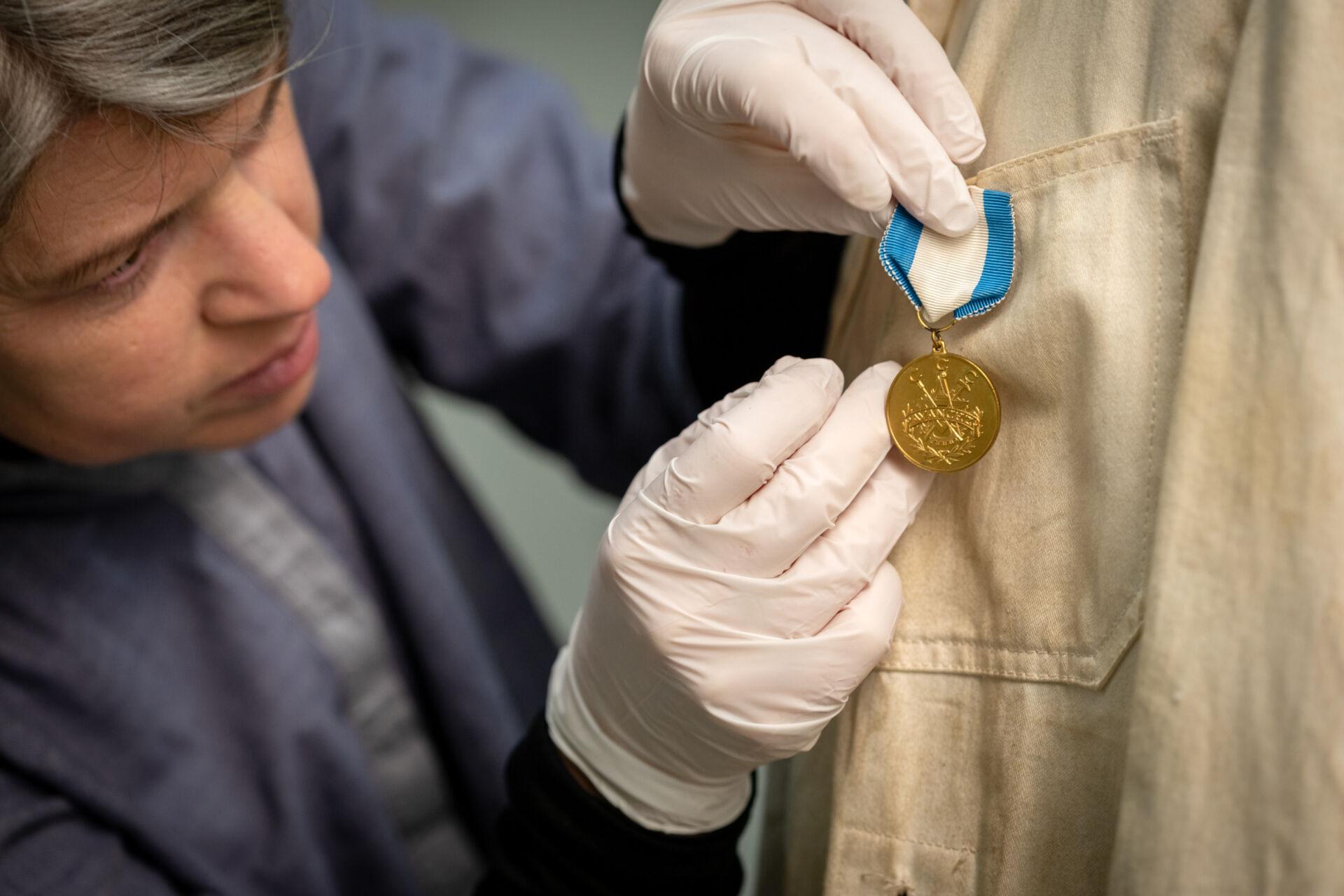 En kvinna med vita handskar synar en medalj på rockens bröstficka