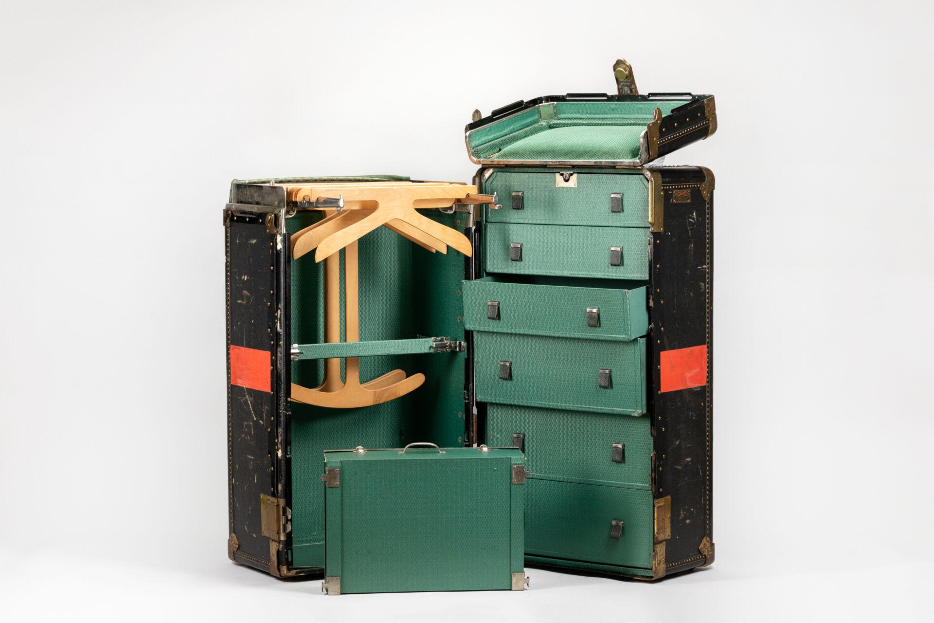 En grön Amerikakoffert på glänt. Utsidan är sliten med bortskrapad färg. Kofferten innehåller en mängd lådor och galgar.