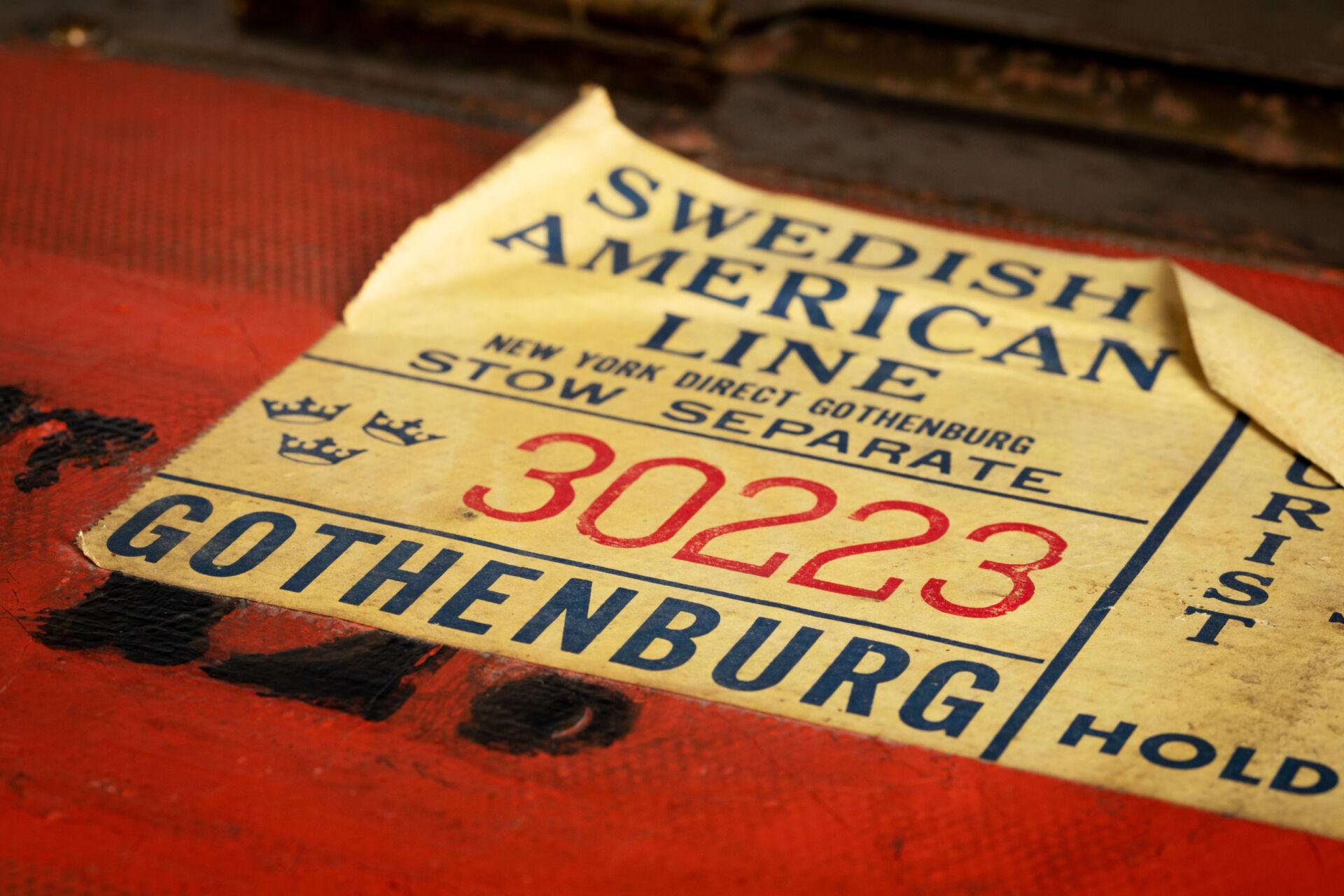Närbild på en klisterlapp där det står Swedish American Line - svenska amerikalinjen