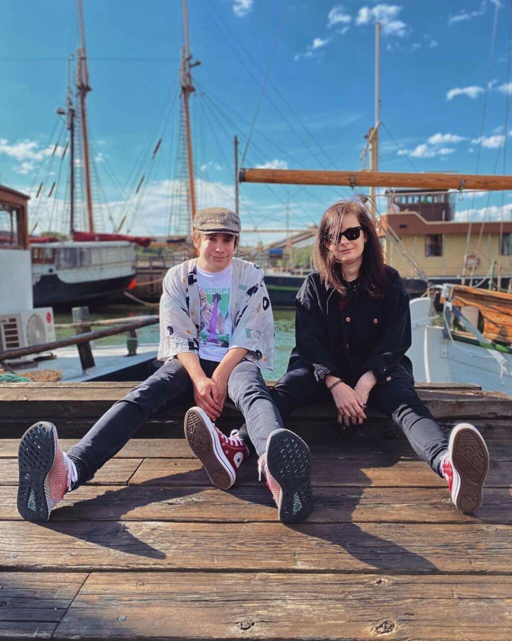 Två personer sitter i hamnen