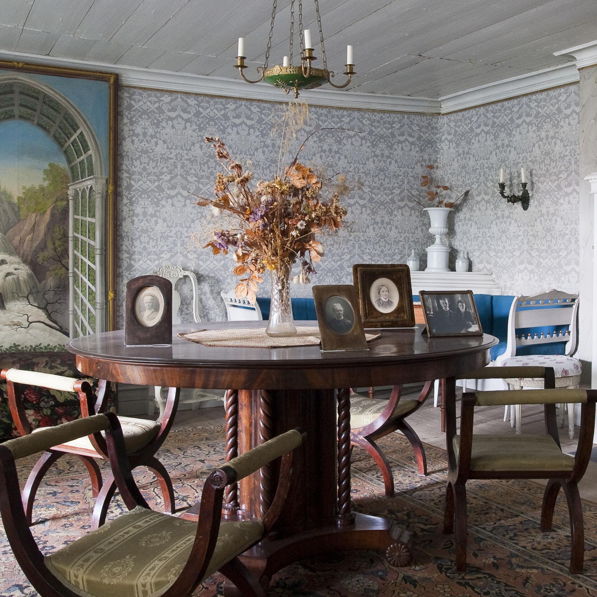 bild ifrån ett av rummen i huset, där vi ser ett bord, fyra stolar, en mönstrad tapet och en stor tavla.