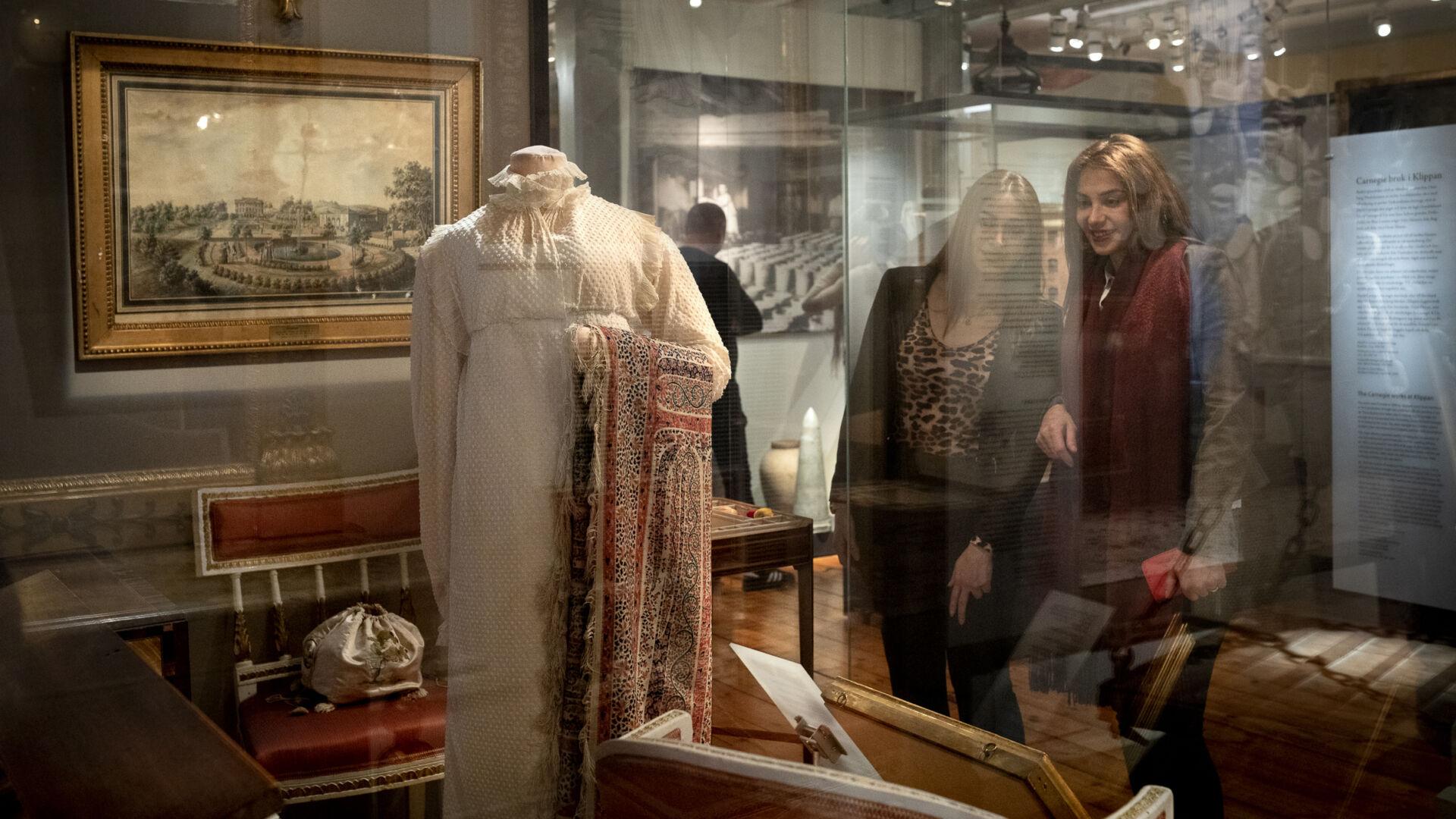 Två kvinnor står och tittar på en vit klänning och några tidstypiska möbler i en glasmonter.