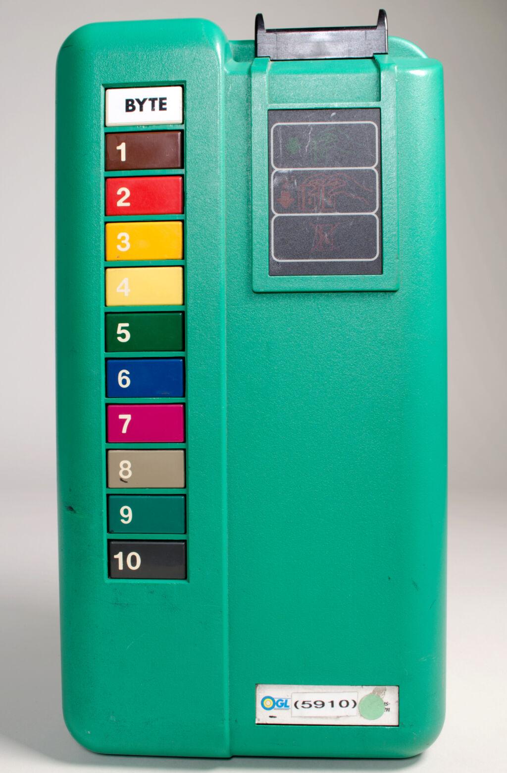 En grön biljettautomat med färgglada knappar från 1990-talet