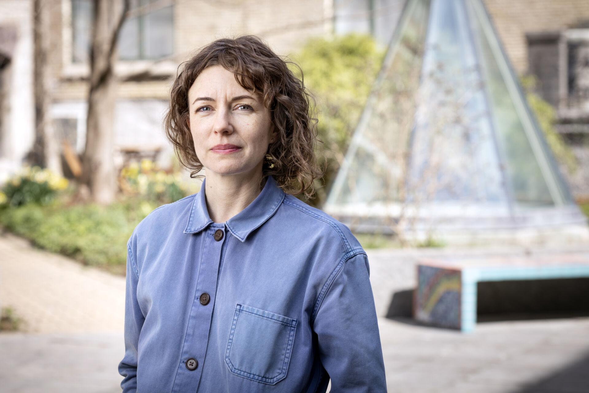 En kvinna med brunt axellång htår och blå skjorta står framför en äldre byggnad