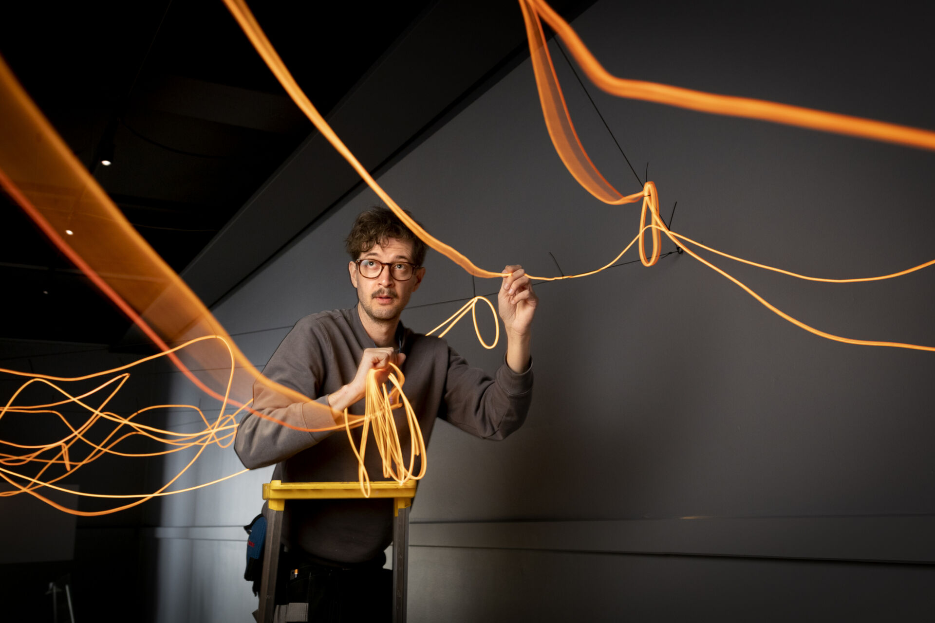 En man med ljust lockigt hår och glasögon står på en stege och håller i ett fång orangelysande trådar som ska fästas i taket