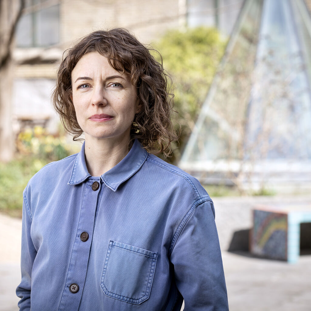 Kvinna med brunt lockigt hår och blå skjorta på en gård