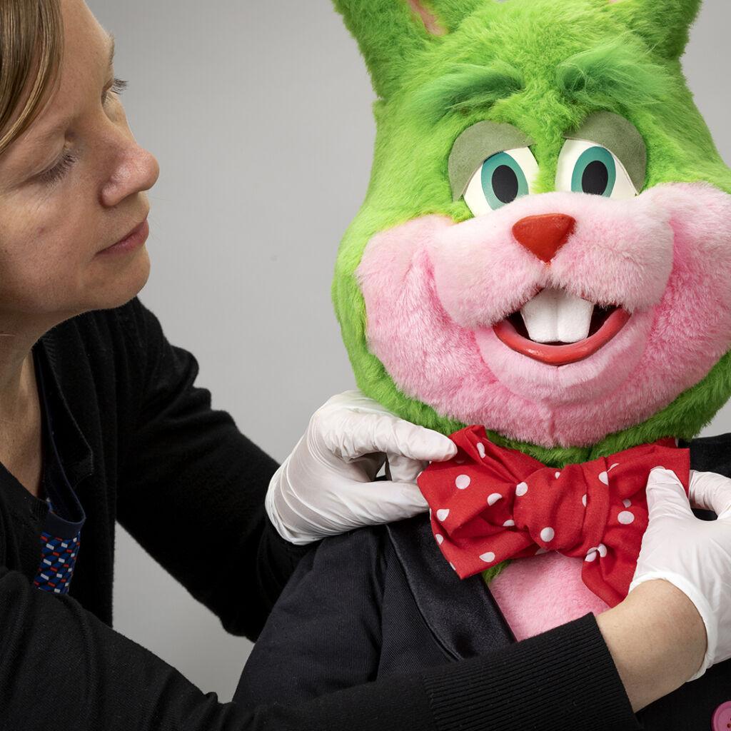En grön kanindocka med prickig fluga som en kvinna med axellångt brunt hår och vita handskar rättar till
